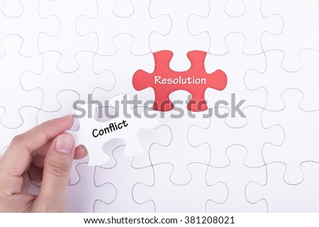 Hand embed missing a piece of puzzle into place, red space with word CONFLICT RESOLUTION. Business and financial concept.