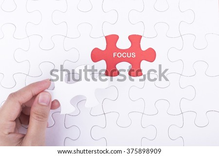 Hand embed missing a piece of puzzle into place, red space with word FOCUS concept.