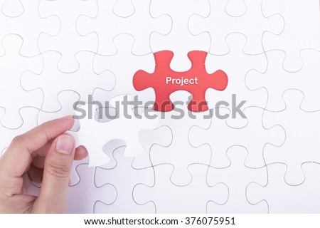Hand embed missing a piece of puzzle into place, red space with word PROJECT concept