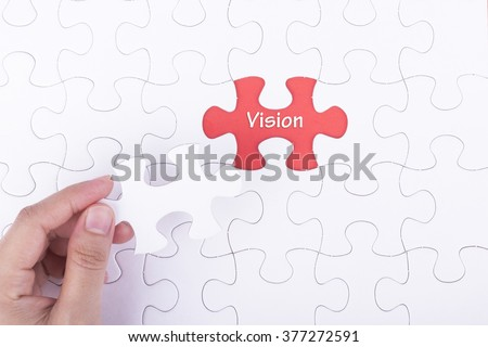 Hand embed missing a piece of puzzle into place, red space with word VISION concept