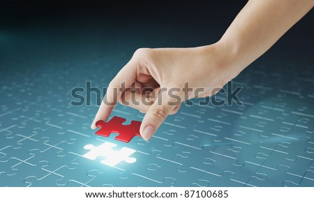 Hand embed missing puzzle piece into place. Business concept for completing the final puzzle place - stock photo