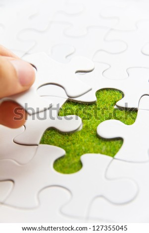 Hand embed missing puzzle piece into place, green space concept - stock photo