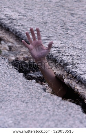 Hand emerging from a crack in the asphalt - stock photo