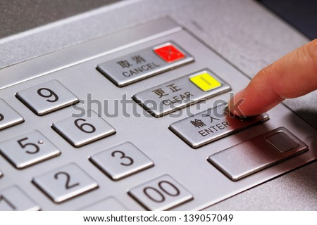 Hand entering personal identification number on ATM dial panel - stock photo