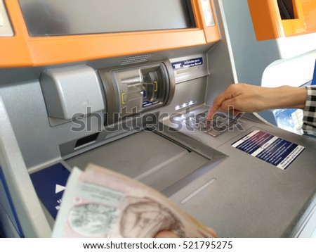 Hand entering PIN numbers on ATM