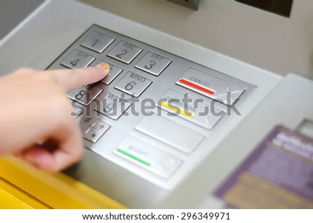 hand entering pins at ATM - stock photo