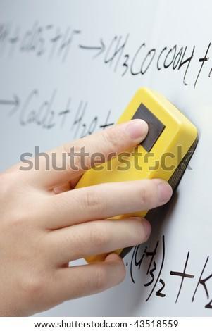 Hand erasing the whiteboard - stock photo