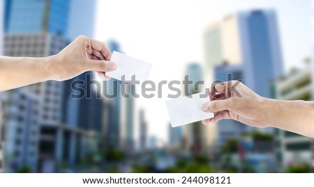 Hand exchanging a card - stock photo