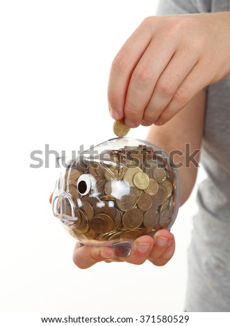 Hand Feeding Piggy Bank - stock photo
