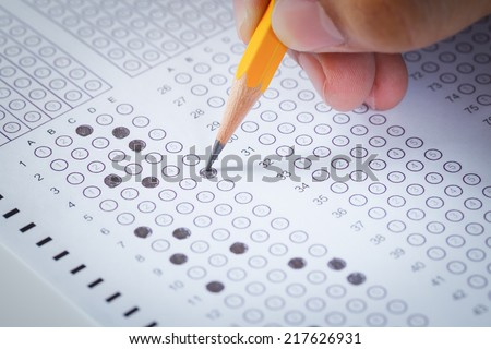 hand fill in Exam carbon paper computer sheet and pencil - stock photo