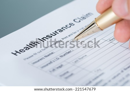 Hand filling health insurance claim form. Closeup shot - stock photo