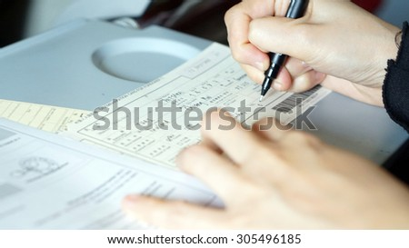 hand filling immigration form on flight to visit country - stock photo