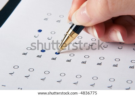 Hand filling in an evaluation form with a pen - stock photo
