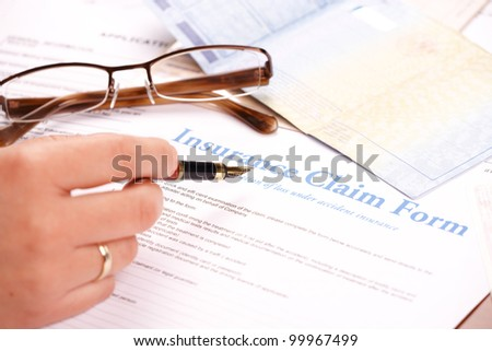 Hand filling in insurance claim form. Glases and other papers like ID or vehicle documents in the background - stock photo