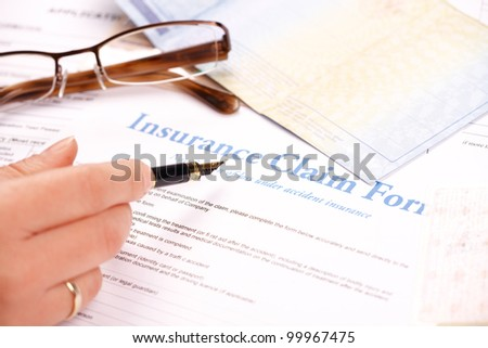 Hand filling in insurance claim form. Other papers like ID or vehicle documents and glases in the background - stock photo