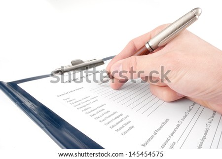 Hand filling in medical questionnaire form in a clipboard isolated on white background  - stock photo