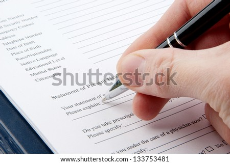 Hand filling in medical questionnaire in a clipboard - stock photo