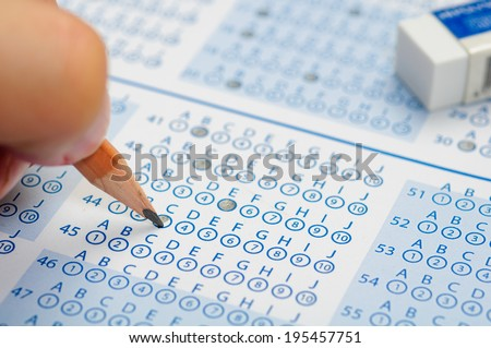 hand filling out answers to standard answer sheet