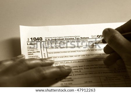 Hand filling 1040 tax form in duo tone color. PS : focus on the tip of pen