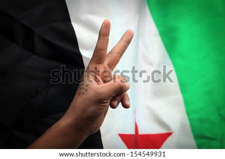 Hand flashes victory sign backdropped by new Syrian flag