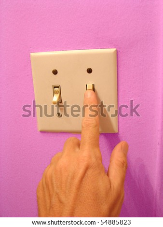 hand flipping light switch with pink wall - stock photo
