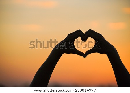 hand forming a heart shape with sunset silhouette - stock photo