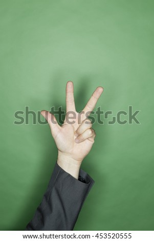 hand gesture of a male caucasian in a business suit:showing the number 3 with fingers - stock photo