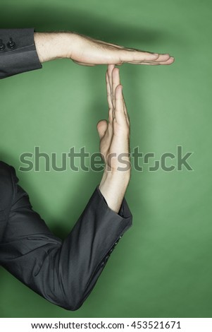 hand gesture of a male caucasian in a business suit: two hands showing T for time out