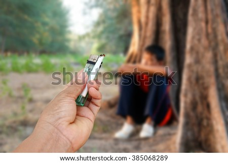 Hand give cigarette to sad boy,the concept of drug problems in youth. - stock photo