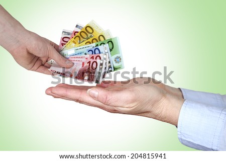 Hand gives money in open hands - stock photo