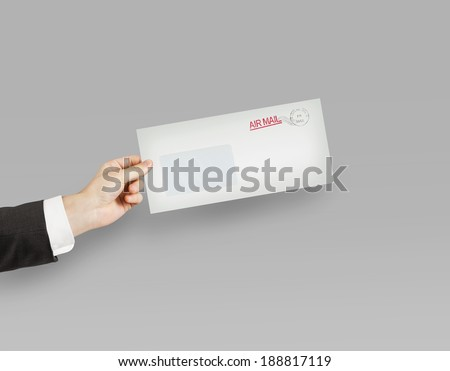 hand giving a envelope on gray background - stock photo