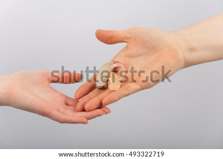Hand giving a hearing aid to another hand