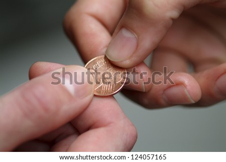 Hand giving 2 cents euro coin to other hand.Shallow focus.
