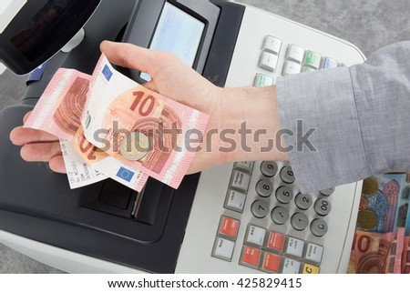 Hand giving change in euro from the till - stock photo