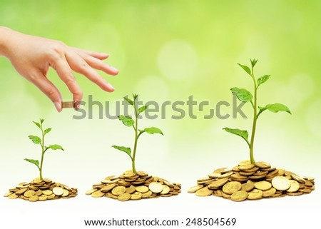 hand giving coins to trees growing on piles of golden coins / business growth with csr practice - stock photo