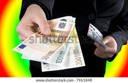 Hand giving Euro banknotes of 50, 100 and 200 Euro with another hand in the background keeping the spare. Colorful casino background. Studio shot.