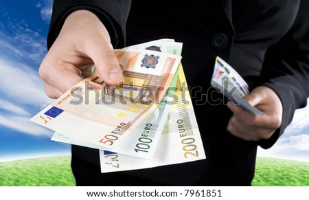 Hand giving Euro banknotes of 50, 100 and 200 Euro with another hand in the background keeping the spare. Studio shot. - stock photo