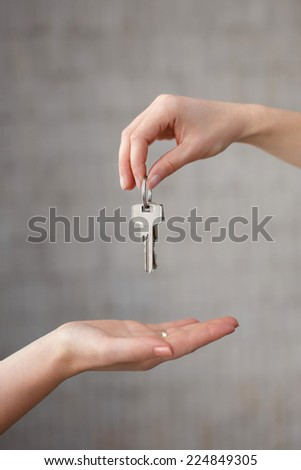 Hand giving keys to another hand in office - stock photo