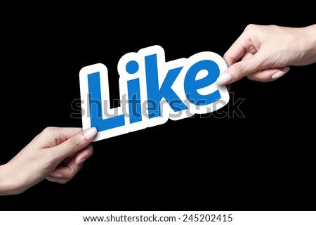 Hand giving like icon to another person - stock photo