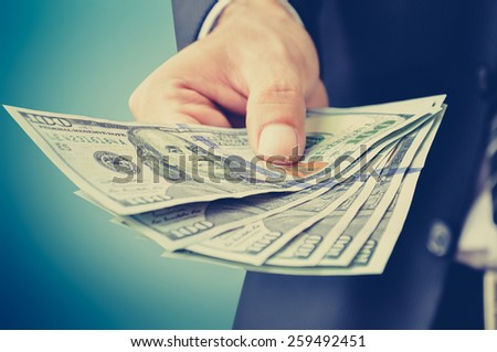 Hand giving money, US dollar (USD) bills - vintage style color effect - stock photo