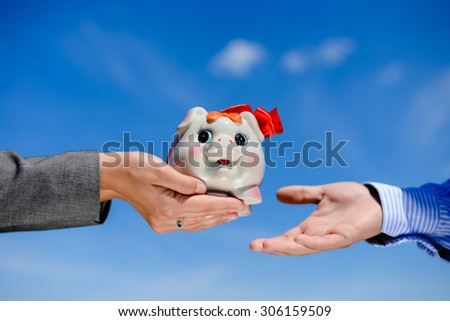 Hand giving piggy bank over blue sky sunny outdoors background copy space - stock photo