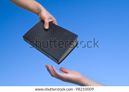 Hand giving the Bible to another person over blue sky - stock photo