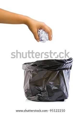 Hand going to drop garbage paper into the bag - stock photo