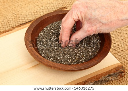 Hand Grabbing A Pinch Of Chia Seeds - stock photo