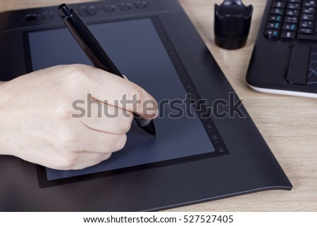 Hand graphic designer with a digital pen and tablet
