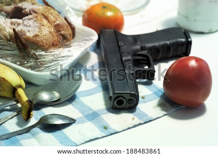 Hand gun laid on a table with food, concept of violence in the families - stock photo