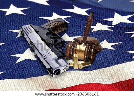 Hand Gun with Gavel and Bullets on American Flag - stock photo