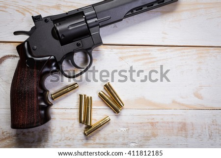 hand gun with rounds on wooden desk - stock photo