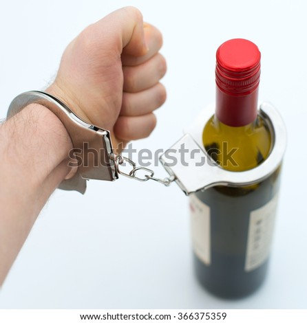 Hand handcuffed to bottle of wine. Alcoholism concept. - stock photo