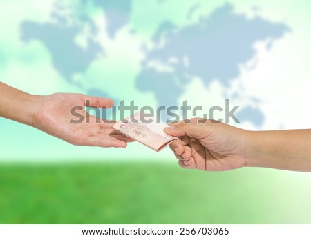 Hand handing over money to another hand  on blurred abstract nature background - stock photo
